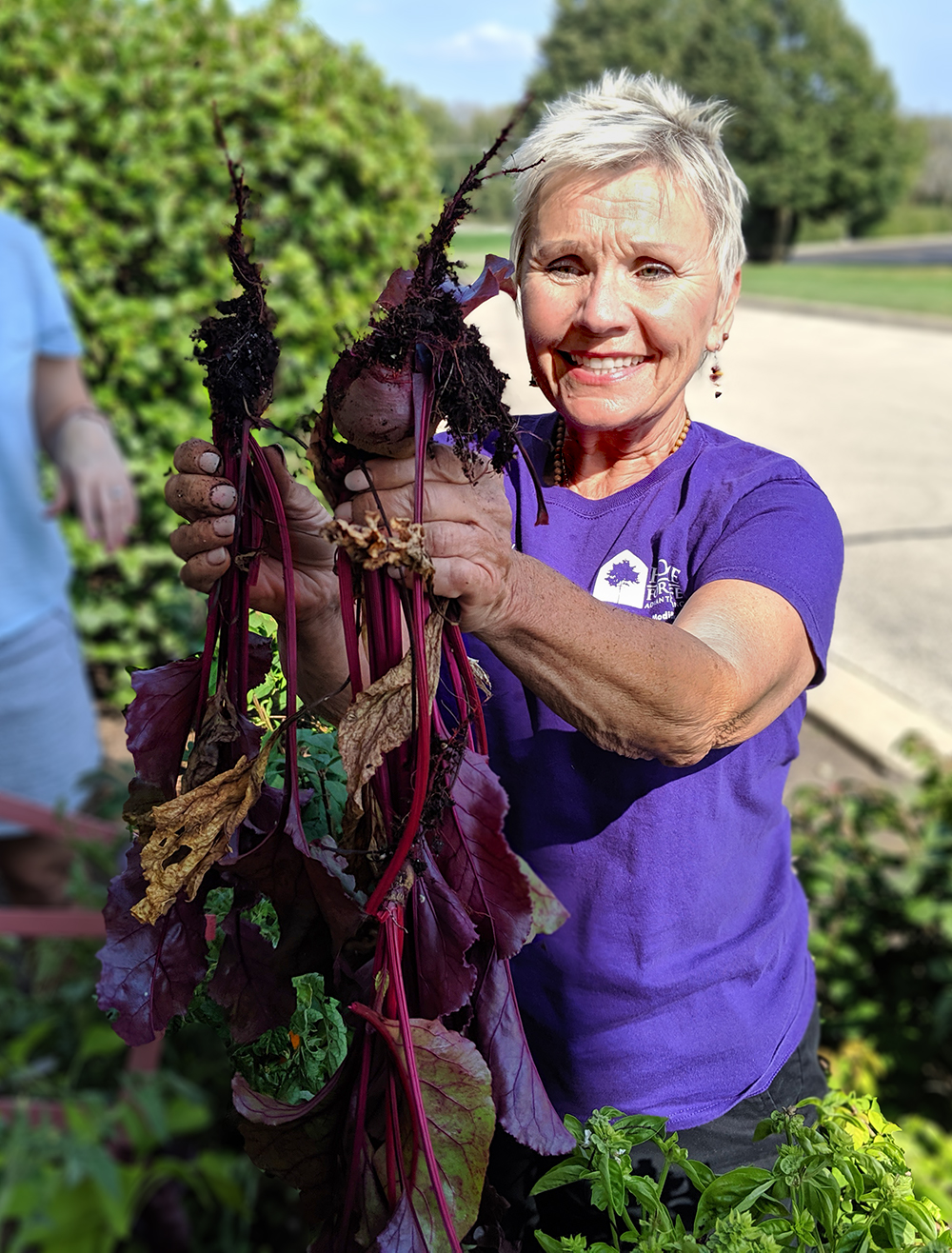 Owner Cindy Shaw holding beats grown in a raised gardening box